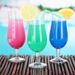 Stock Photo: Glasses of cocktails on table near pool