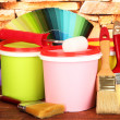 Set for painting: paint pots, brushes, paint-roller, palette of colors on stone wall background — Stock Photo