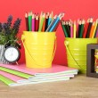 Colorful pencils in two pails with copybooks on table on red background — Foto Stock