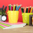 Colorful pencils in two pails with copybooks on table on red background — Stock Photo #22793448