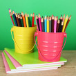 Colorful pencils in two pails with copybooks on table on green background — Stock Photo