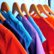 Stock Photo: Lots of T-shirts on hangers on blue background