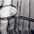 Magnifying glass over the stack of books in grey light — Stock Photo #22796948