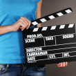 Movie production clapper board in hands on grey background — 图库照片