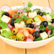 Fresh salad in plate on wooden table — Stock Photo #22797628