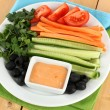 Assorted raw vegetables sticks in plate on wooden table close up - Stock Photo