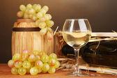 Cassa in legno con bottiglia di vino, botte, bicchiere da vino e dell'uva sul tavolo di legno su sfondo marrone — Foto Stock