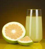 Heerlijke lieverd sap in glas en lieverd ernaast op donker oranje achtergrond — Stockfoto