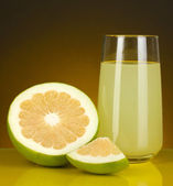 Delicious sweetie juice in glass and sweetie next to it on dark orange background — Stock Photo