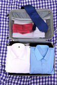 Open grey suitcase with clothing on plaid — Stock Photo