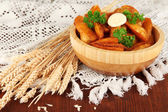 Appetizing village potatoes in bowl on wooden table close-up — Stock Photo