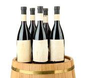Wine bottles on wooden barrel, isolated on white — Stock Photo