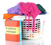 Clothes with washing powder in plastic basket isolated on white — Stock Photo