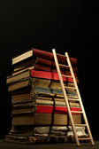 Old books and wooden ladder, on black background — Stock Photo