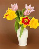 Beautiful tulips in bucket on brown background — Stock Photo