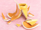 Yellow broken cup on table on pink background — Stok fotoğraf