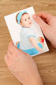 Photos in hands on wooden table — Stock Photo