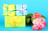 Pink tulips and gift boxes, on color background — Stock Photo