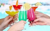 коктейли в руках на фоне бассейна — Стоковое фото