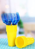 Cups, spoons and forks, of different colors on bright background — Stock Photo