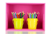 Colorful pencils in pails on shelf isolated on white — Stock Photo