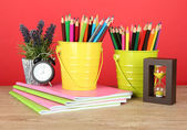 Colorful pencils in two pails with copybooks on table on red background — Zdjęcie stockowe