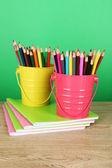 Lápices de colores en dos cubos con cuadernos en mesa sobre fondo verde — Foto de Stock