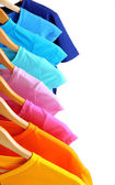 Lots of T-shirts on hangers isolated on white — Stock Photo