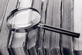 Magnifying glass over the stack of books in grey light — Stock Photo