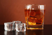 Glass of whiskey and ice on brown background — Stock Photo