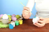 Young woman painting Easter eggs, on color background — Стоковое фото