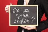Młoda kobieta trzyma znak czy mówisz po angielsku? — Zdjęcie stockowe