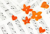 Decorative flowers and hearts from dry orange peel on musical notes — Stock Photo