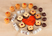 Sweet cookies with valentine card on wooden background — Stock Photo