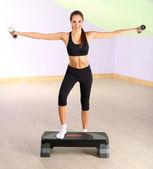 Młoda kobieta robi ćwiczenia fitness na silnik krokowy w gimnazjum — Zdjęcie stockowe