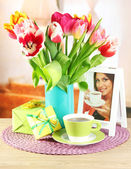 Beautiful tulips in bucket with gifts and cup of tea on table in room — Foto de Stock