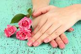 Frau hände mit rosa maniküre und blumen, auf farbigem hintergrund — Stockfoto