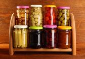 Diferentes conservaciones en estanterías sobre fondo de madera — Foto de Stock