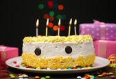 Pastel de feliz cumpleaños y regalos, sobre fondo negro — Foto de Stock