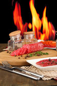 Tasty salami on plate and board on wooden table on fire background — Stock Photo