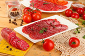 Tasty salami on plates on wooden table close-up — Stock Photo