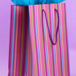 Striped shopping bag on purple background — Stock Photo