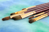 Brushes on bright abstract gouache painted background — Stock Photo