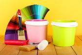 Paint pots, paintbrushes and coloured swatches on wooden table on yellow background — Stock Photo