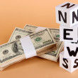 Foto Stock: White paper cubes labeled News with money on beige background