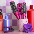 Hair brushes, hair straighteners and cosmetic bottles in bathroo — Stock Photo