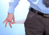 Business man showing his empty pocket, on blue background — Stock Photo