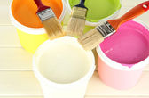 Set for painting: paint pots, brushes on white wooden table — Stock Photo