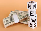 White paper cubes labeled News with money on beige background — Foto Stock