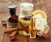 Bottles with ingredients for the perfume on wooden background — Stock Photo